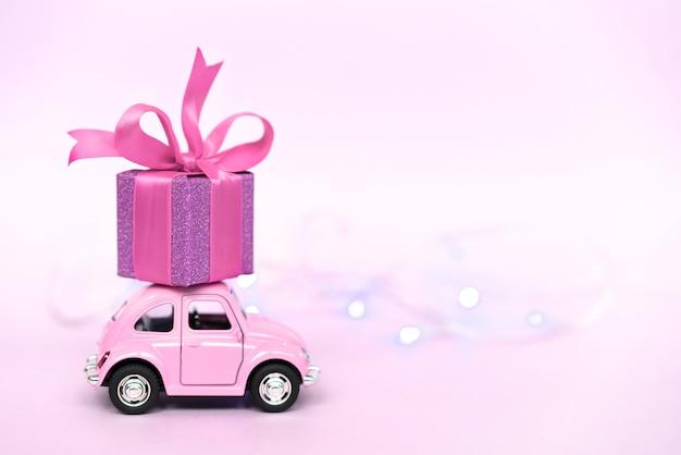 Różowy retro samochodzik dostarczający pudełko na walentynki na różowo