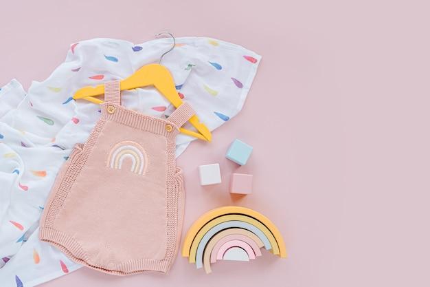 Różowy romper dzianinowy na wieszaku z tęczowymi i drewnianymi zabawkami. zestaw ubranek i akcesoriów dla niemowląt na wiosnę lub lato. moda dla dzieci. płaski układanie, widok z góry