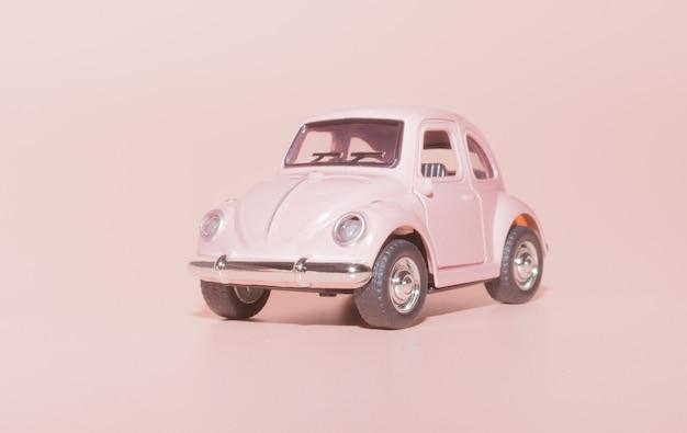 Różowy samochód retro zabawka zbliżenie na różowym tle
