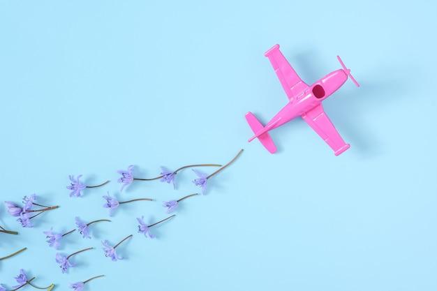 Różowy samolot nabiera ostrego zakrętu na niebieskim tle