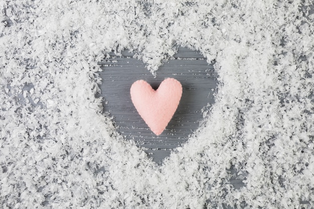 Różowy serce między dekoracyjnym śniegiem na drewnianym biurku
