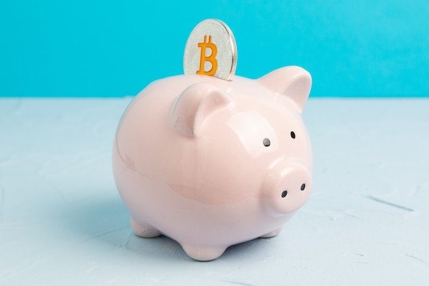Różowy skarbonka na niebieskiej przestrzeni z monetą bitcoin