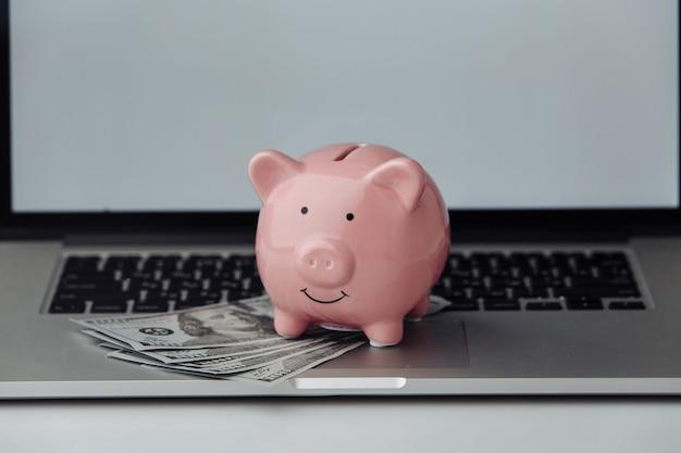 Różowy skarbonka z laptopem. koncepcja biznesowa online
