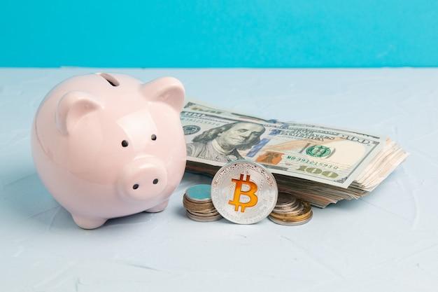 Różowy skarbonka z monetą bitcoin i dolarami