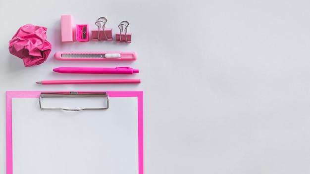 Różowy skład z materiałów biurowych na stole