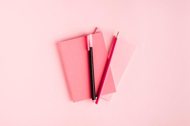 Różowy skład z notatnikiem i materiały piśmienne na biurku