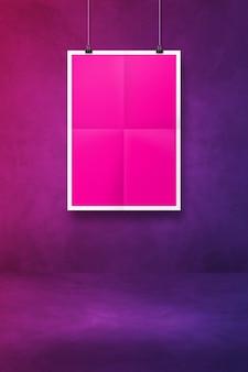 Różowy składany plakat wiszący na fioletowej ścianie z klipsami. pusty szablon makiety