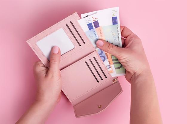 Różowy skórzany portfel z pieniędzmi euro w kobiecych rękach, koncepcja pieniędzy, finanse, zakupy, gotówka