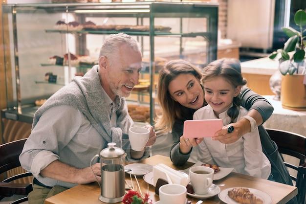 Różowy smartfon. piękna babcia trzyma swojego różowego smartfona, pokazując zdjęcia wnuczce