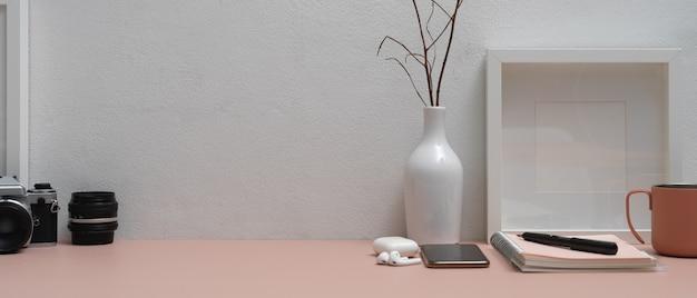 Różowy stół roboczy z papeterią, smartfonem, aparatem, akcesoriami, dekoracjami i miejscem na kopię
