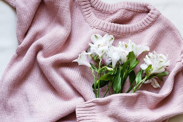 Różowy sweter z dzianiny i białe kwiaty