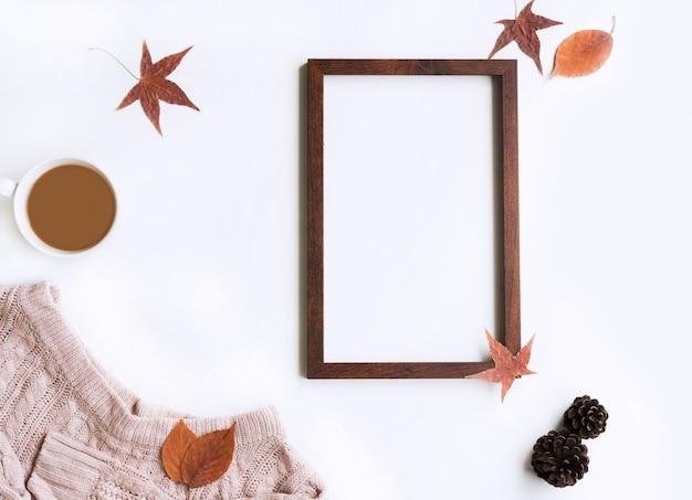 Różowy sweter z dzianiny i suszone liście klonu z płomieniem na wiadomość tekstową na białym tle, leżał płasko, widok z góry, miejsce