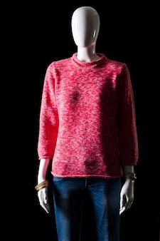 Różowy sweter z niebieskimi dżinsami. dżinsy i pulower na manekinie. jasny damski strój na wiosnę. ciepłe kolory i prosty wzór.