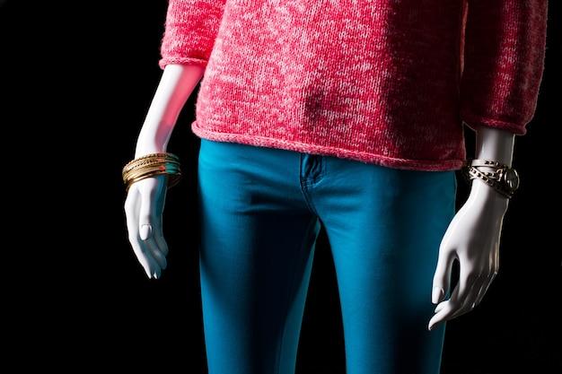 Różowy sweter, zegarek i bransoletka. manekin ubrany w sweter i akcesoria. ciepły ubiór damski na wiosnę. klasyczny zegarek i złota bransoletka.