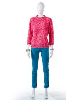 Różowy sweterek i turkusowe spodnie. żeński manekin na sobie różową bluzę. modny damski strój na wiosnę. sweter z długim rękawem na gablocie.