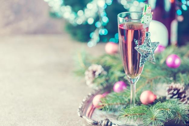 Różowy szampan w kieliszku i ozdoby świąteczne