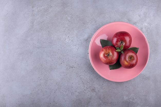 Różowy talerz dojrzałych czerwonych jabłek umieszczony na kamieniu.