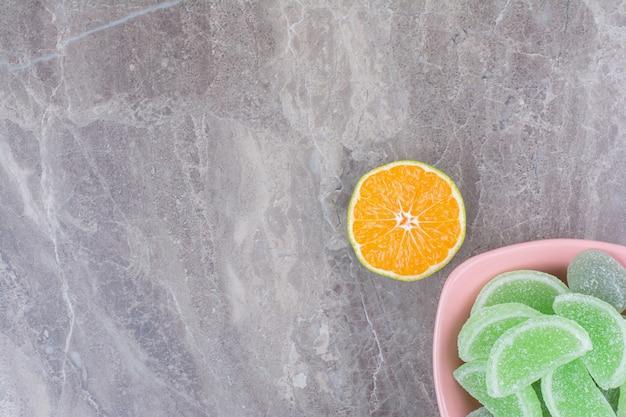 Różowy talerz marmolady i plasterek pomarańczy na tle marmuru.