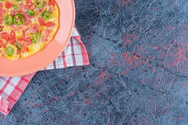 Różowy talerz omletu z warzywami.
