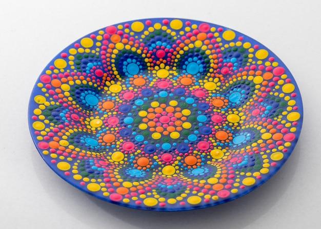 Różowy talerz ozdobny z wzorem w stylu mandali do dekoracji wnętrz, na białym tle
