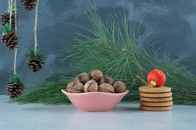 Różowy talerz pełen orzechów włoskich i słodkich ciasteczek na marmurowym tle. wysokiej jakości zdjęcie