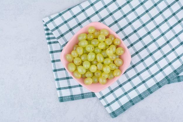 Różowy talerz pełen zielonych pysznych winogron. zdjęcie wysokiej jakości