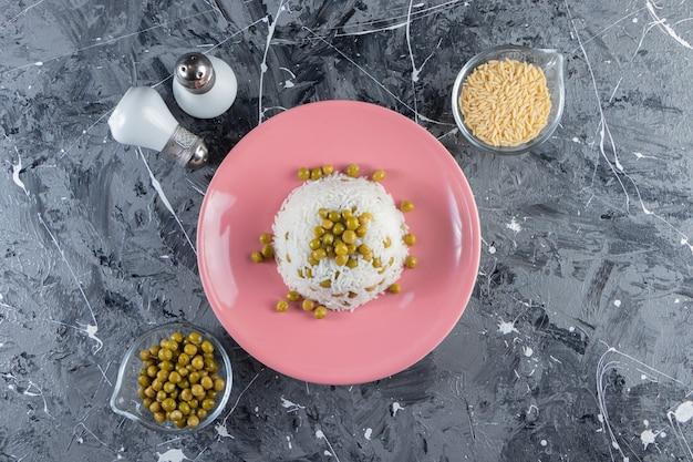 Różowy talerz z gotowanym ryżem i zielonym groszkiem na tle marmuru.