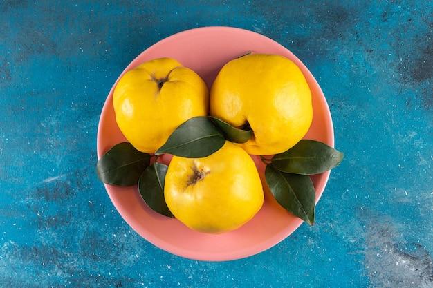 Różowy talerz z trzema żółtymi owocami pigwy na niebieskim tle.