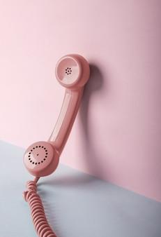 Różowy telefon vintage na przestrzeni niebieskiej i różowej