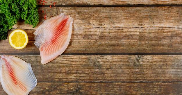 Różowy tilapia z cytryną i kale na drewnianym tle.