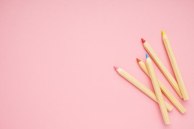 Różowy tło z drewnianymi kolorowymi zwyczajnymi ołówkami. powrót do szkoły.