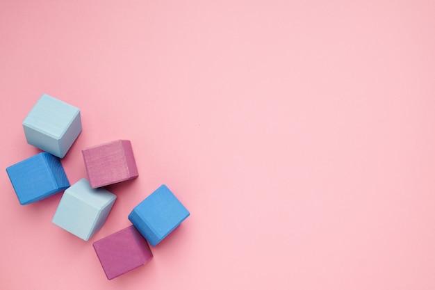 Różowy tło z kolorowymi drewnianymi sześcianami. zabawki kreatywne. klocki dla dzieci.