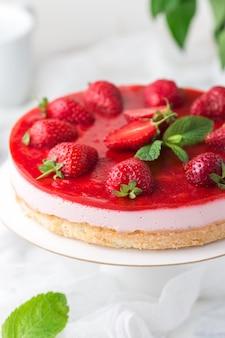 Różowy tort musowy z galaretką jagodową ozdobiony świeżymi truskawkami na stojaku z białym ciastem