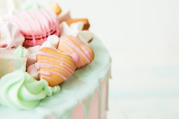 Różowy tort z serduszkami, makaronikami i piankami. selektywna ostrość
