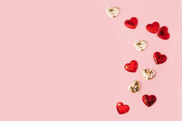 Różowy transparent z miejsca kopiowania i biały koniec czerwone błyszczące serca na nim. koncepcja karty z pozdrowieniami.