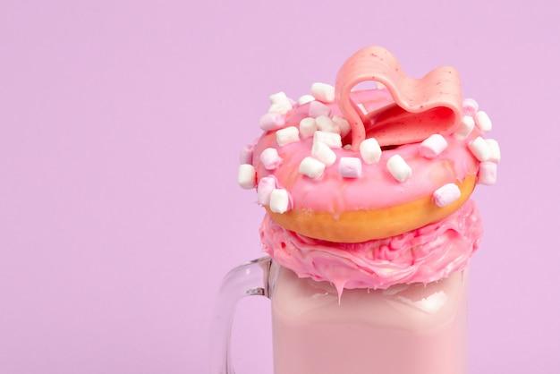 Różowy truskawkowy freakshake z pianką i słodyczami.