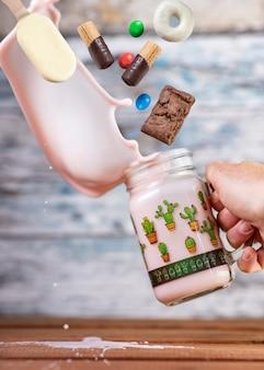 Różowy truskawkowy freakshake ze słodyczami w powietrzu spada