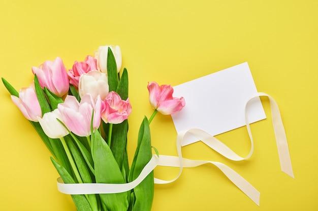 Różowy tulipan bukiet kwiatów przed żółtym tle.