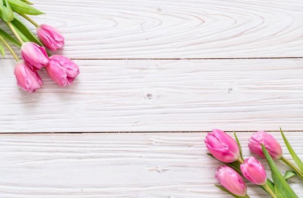 Różowy tulipan kwiat na tle drewna