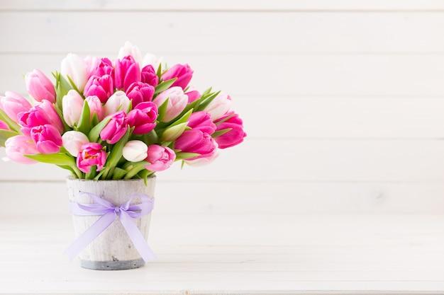 Różowy tulipan na białym na białym tle. kartkę z życzeniami wielkanocnych i wiosennych.