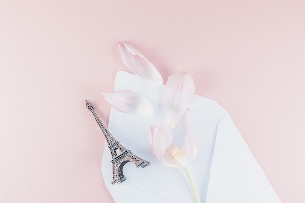Różowy tulipan w kopercie z miniaturą wieży eiffla