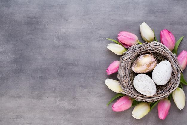Różowy tulipan z różowymi jajkami gniazdo na szarym tle.