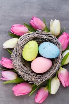 Różowy tulipan z różowymi jajkami gniazduje na szarej kartce z życzeniami wielkanocnymi.