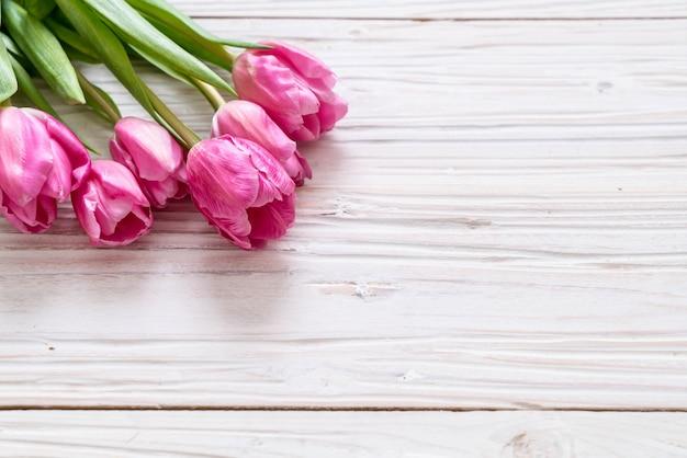 Różowy tulipanowy kwiat na drewnie