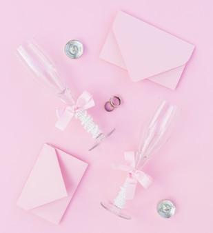 Różowy układ weselny z kieliszkami do szampana i zaproszeniami