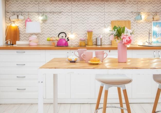 Różowy wazon z kwiatami i kubkami na herbatę na stole w jasnej kuchni w stylu skandynawskim.