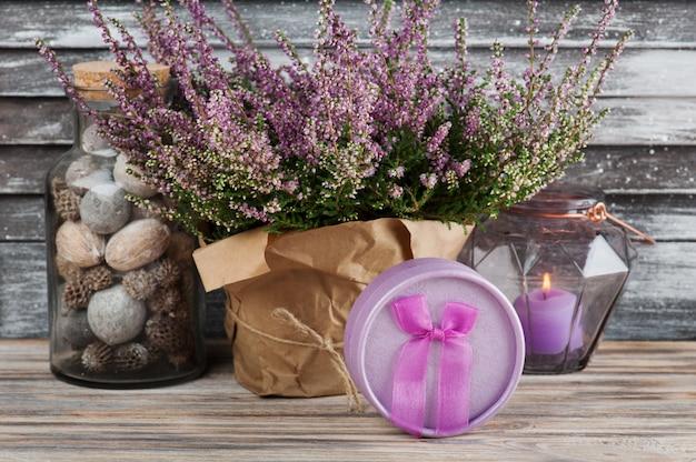 Różowy wrzos i świeca w geometrycznym szklanym wazonie