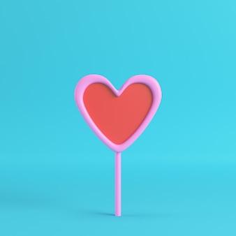 Różowy z czerwonym sercem na patyku na jasnym niebieskim tle