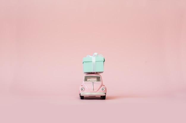 Różowy zabawkarski retro wzorcowy samochód dostarcza prezenta pudełko na różowym tle