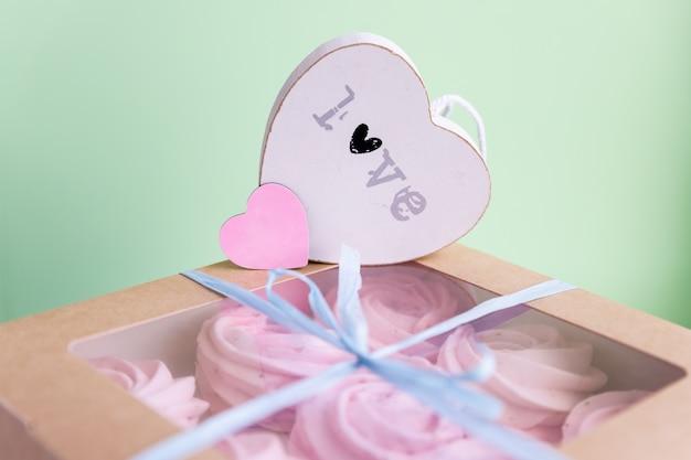 Różowy zefir lub ptasie mleczko w pudełku, z bliska. smaczne jedzenie. pasztet, beza, zefir. koncepcja walentynki lub dzień matki. prezent z sercem. miłość i uczucia